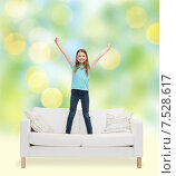 Купить «smiling little girl jumping on sofa», фото № 7528617, снято 9 апреля 2014 г. (c) Syda Productions / Фотобанк Лори