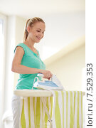Купить «happy woman with iron and ironing board at home», фото № 7529353, снято 25 января 2015 г. (c) Syda Productions / Фотобанк Лори