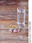 Купить «pills and capsules with glass of water on table», фото № 7533181, снято 14 мая 2015 г. (c) Syda Productions / Фотобанк Лори