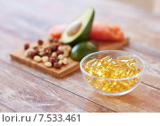 Купить «close up of omega 3 capsules and food on table», фото № 7533461, снято 14 мая 2015 г. (c) Syda Productions / Фотобанк Лори