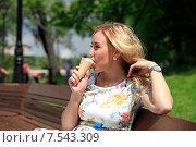 Молодая женщина ест мороженое в парке солнечным летним днем. Стоковое фото, фотограф Яна Королёва / Фотобанк Лори
