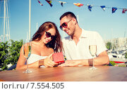 smiling couple with champagne and gift at cafe. Стоковое фото, фотограф Syda Productions / Фотобанк Лори