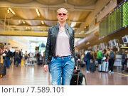 Купить «Женщина с чемоданом идет по терминалу аэропорта», фото № 7589101, снято 20 августа 2018 г. (c) Matej Kastelic / Фотобанк Лори
