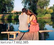 Купить «Молодая пара сидит на мосту около реки», фото № 7602385, снято 13 июня 2015 г. (c) Юрий Плющев / Фотобанк Лори