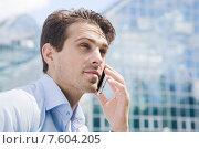 Купить «Молодой привлекательный мужчина разговаривает по телефону на фоне современного здания», фото № 7604205, снято 9 июня 2015 г. (c) Дмитрий Булин / Фотобанк Лори