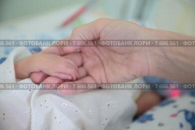 Московский областной перинатальный центр в Балашихе. Мама ухаживает за своим ребенком, фокус на ручке младенца