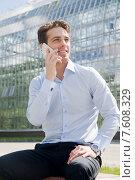 Купить «Молодой бизнесмен разговаривает по телефону на фоне современного офисного здания», фото № 7608329, снято 9 июня 2015 г. (c) Дмитрий Булин / Фотобанк Лори