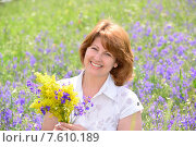 Купить «Красивая счастливая женщина средних лет собирает полевые цветы на лугу», фото № 7610189, снято 23 июня 2015 г. (c) Володина Ольга / Фотобанк Лори