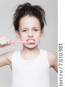 Купить «Маленькая девочка чистит зубы зубной щеткой на сером фоне», фото № 7610981, снято 13 мая 2015 г. (c) Дмитрий Булин / Фотобанк Лори