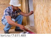 Купить «Строитель измеряет дверную коробку в незавершенном доме», фото № 7611489, снято 19 октября 2018 г. (c) Вячеслав Николаенко / Фотобанк Лори