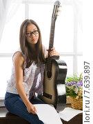 Купить «Young student girl playing music on guitar», фото № 7639897, снято 24 июня 2015 г. (c) Владимир Мельников / Фотобанк Лори