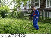 Подросток в деревне косит траву бензокосой. Стоковое фото, фотограф Данилова Наталья / Фотобанк Лори
