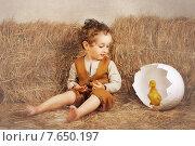 Мальчик сидит среди брикетов соломы, утёнок в большом яйце. Стоковое фото, фотограф Olena Kravchuk / Фотобанк Лори