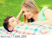 Купить «smiling couple lying on blanket in park», фото № 7666269, снято 7 июля 2014 г. (c) Syda Productions / Фотобанк Лори