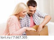 Купить «happy couple with parcel box at home», фото № 7667305, снято 6 июня 2015 г. (c) Syda Productions / Фотобанк Лори