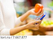 Купить «woman with smartphone and persimmon in market», фото № 7667877, снято 20 декабря 2014 г. (c) Syda Productions / Фотобанк Лори