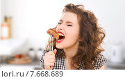 Купить «hungry young woman eating meat on fork in kitchen», фото № 7668689, снято 3 января 2010 г. (c) Syda Productions / Фотобанк Лори