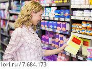Купить «Smiling pretty woman looking at a product», фото № 7684173, снято 21 января 2015 г. (c) Wavebreak Media / Фотобанк Лори