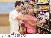 Купить «Smiling bright couple buying food products showing shelf», фото № 7685273, снято 21 января 2015 г. (c) Wavebreak Media / Фотобанк Лори