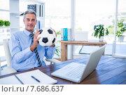 Купить «Happy businessman looking at camera and holding foot ball», фото № 7686637, снято 17 марта 2015 г. (c) Wavebreak Media / Фотобанк Лори