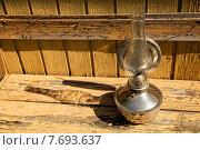 Старая керосиновая лампа на фоне желтой облупившейся старой стены. Стоковое фото, фотограф Владимир Ходатаев / Фотобанк Лори