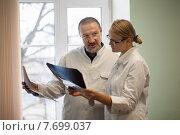 Купить «Два врача с рентгеновскими снимками в холле больницы», фото № 7699037, снято 3 апреля 2015 г. (c) Данил Руденко / Фотобанк Лори