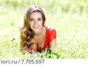 Купить «Красивая девушка в красном платье лежит на траве в летнем парке», фото № 7705697, снято 10 июня 2015 г. (c) Иван Михайлов / Фотобанк Лори
