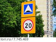 Купить «Дорожные знаки Искусственная неровность и Ограничение максимальной скорости в городе на фоне дома и деревьев», эксклюзивное фото № 7745469, снято 12 июня 2015 г. (c) Наталья Горкина / Фотобанк Лори