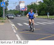 Велосипедистка двигается по проезжей части дороги. Вешняковская улица. Москва (2014 год). Редакционное фото, фотограф lana1501 / Фотобанк Лори
