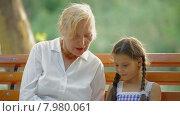 Купить «Бабушка читает книгу внучке в парке», видеоролик № 7980061, снято 20 июня 2015 г. (c) Tatiana Kravchenko / Фотобанк Лори