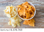 Купить «close up of potato crisps and corn nachos on table», фото № 8378769, снято 22 мая 2015 г. (c) Syda Productions / Фотобанк Лори