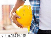 Купить «close up of builder hand holding hardhat outdoors», фото № 8380445, снято 21 сентября 2014 г. (c) Syda Productions / Фотобанк Лори