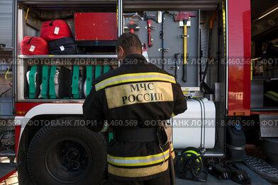 Сотрудник МЧС во около пожарной машины во время тушения пожара