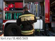 Купить «Сотрудник МЧС во около пожарной машины во время тушения пожара», фото № 8460569, снято 24 июля 2015 г. (c) Николай Винокуров / Фотобанк Лори