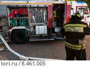 Купить «Сотрудник МЧС в полной экипировке стоит около пожарной машины во время тушения пожара», фото № 8461005, снято 24 июля 2015 г. (c) Николай Винокуров / Фотобанк Лори