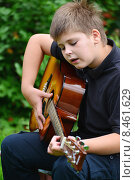 Купить «Летним днем подросток играет на гитаре и поет на открытом воздухе», фото № 8461629, снято 21 июля 2015 г. (c) Володина Ольга / Фотобанк Лори