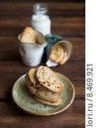 Традиционное домашнее итальянское кантуччи - печенье с миндалем на небольшой тарелке и в маленьких чашечках на деревянном столе. Стоковое фото, фотограф Анна Курзаева / Фотобанк Лори
