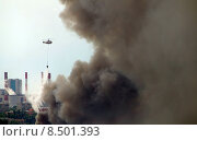 Пожарный вертолет сбрасывает воду на место пожара. Пожар на заводе ЗИЛ в Москве (2015 год). Редакционное фото, фотограф Александр Ледовской / Фотобанк Лори
