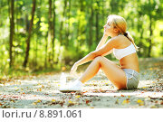 Купить «Woman Runner Resting on a Forest Path», фото № 8891061, снято 23 октября 2018 г. (c) PantherMedia / Фотобанк Лори