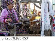 Купить «Пожилая женщина ткет на старинном станке тряпичный коврик из лоскутов ткани на улице, Россия», фото № 8985053, снято 8 августа 2015 г. (c) Николай Винокуров / Фотобанк Лори