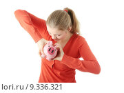 Купить «Young blond woman trying to get money from her piggy bank, isolated on white background », фото № 9336321, снято 24 апреля 2019 г. (c) PantherMedia / Фотобанк Лори