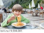 Купить «Мальчик ест макароны Болоньезе на террасе кафе», фото № 9594081, снято 22 июля 2015 г. (c) Юлия Кузнецова / Фотобанк Лори