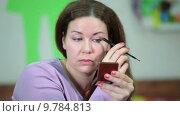 Купить «Молодая женщина наносит тени на веки глаз, смотрит в зеркальце», видеоролик № 9784813, снято 22 июня 2015 г. (c) Кекяляйнен Андрей / Фотобанк Лори