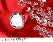 Купить «A variety of clear sparkling diamonds on a red satin background.», фото № 9790241, снято 14 июля 2018 г. (c) PantherMedia / Фотобанк Лори