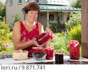 Купить «Счастливая женщина на даче показывает свежее варенье из малины», фото № 9871741, снято 1 августа 2015 г. (c) Алексей Кузнецов / Фотобанк Лори
