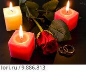 wedding rings rose and candles in night. Стоковое фото, фотограф Sergej Razvodovskij / PantherMedia / Фотобанк Лори