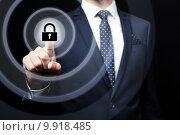 Бизнесмен нажимает кнопку с символом замка на виртуальном экране. Стоковое фото, фотограф Евдокимов Максим / Фотобанк Лори