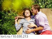 Portrait of happy young couple lying on straw rug outside. Стоковое фото, фотограф Dmitriy Shironosov / PantherMedia / Фотобанк Лори