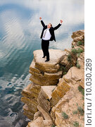 Купить «Photo of happy businessman standing on the mountain and raising his hands », фото № 10030289, снято 17 февраля 2020 г. (c) PantherMedia / Фотобанк Лори
