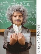Купить «Little Einstein holding books in front of chalkboard», фото № 10165485, снято 8 июля 2015 г. (c) Wavebreak Media / Фотобанк Лори